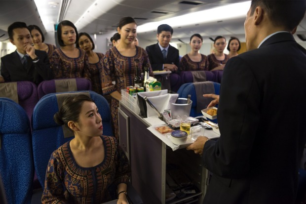 Inside Singapore Airlines flight school: New recruit are shown how to conduct meal service.