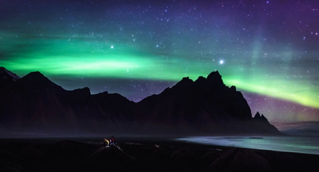 A pair of Japanese travellers watch from a black sand dune as the northern lights dance over Vestrahorn Mountain in East ...