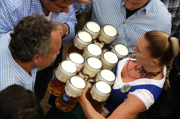 A waitress carries beer mugs during the opening of the 184th Oktoberfest beer festival in Munich, Germany.