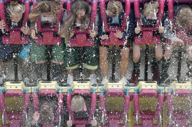 Young people ride a fairground ride behind a fountain on the opening day of the 184th Oktoberfest beer festival in ...