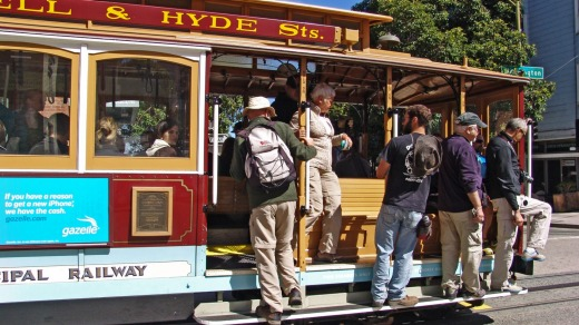 People and tourists travel on the side footboard of the famous cable car bus on a sunny September day in San Francisco.