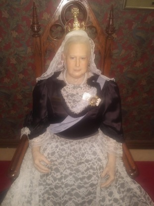 Queen Victoria, deep in thought, on the throne.