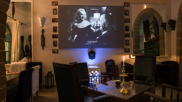 Movies play in a high-ceilinged restaurant that feels like a gentleman's club with its black-and-white decor and Berber ...