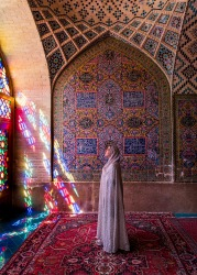 A woman bathes in the morning light in one of Iran's most beautiful mosques the Nasir Al-Mulk Mosque in Shiraz which is ...