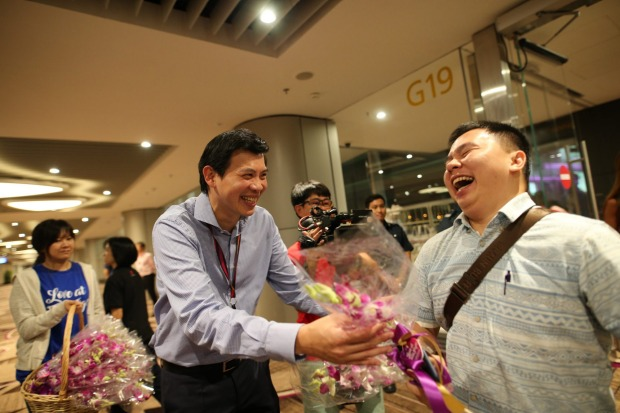 CEO of Changi Airport Group Lee Seow Hiang welcomes passengers on T4's first arrival flight with orchids.