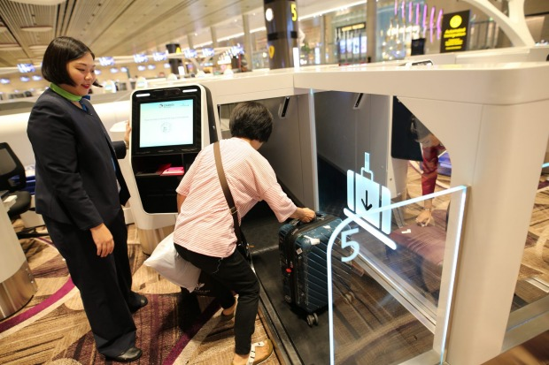 A departing passenger drops her check-in bag at the automated bag-drop at the new Terminal 4.