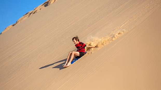 Enjoy sand boarding on the towering dunes at Port Stephens.