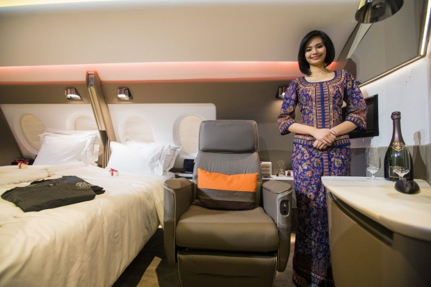 A flight attendant poses with a mock up of the first class suite during its unveiling in Singapore.