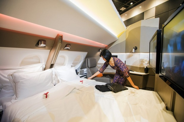 A flight attendant arranges a bed in two adjoining mock-up first class suites.