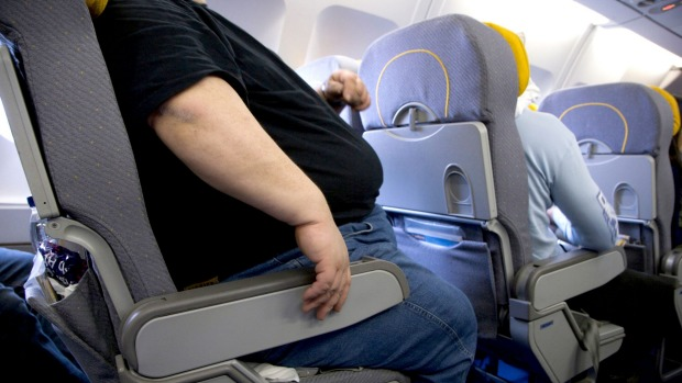 If a passenger cannot fit into the seat with the armrests down, they should buy two seats, says a reader.