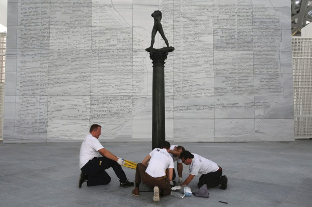 """Museum specialists fix the """"Walking Man, On a Column"""" of Auguste Rodin, made in 2006 by Fonderie Coubertin at the Louvre ..."""