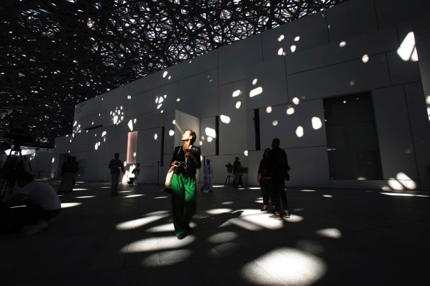 A journalist walks under the lights coming through of the dome at the Louvre Abu Dhabi, United Arab Emirates.