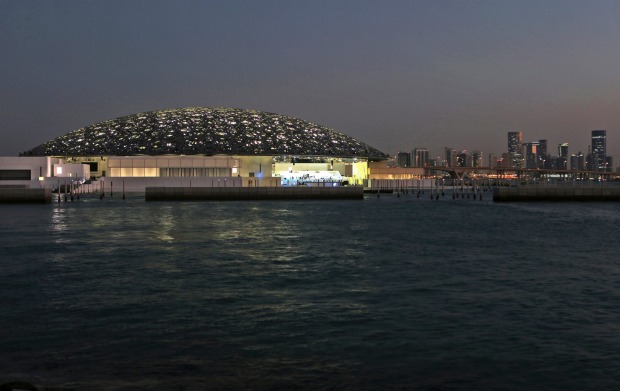 The night view of Louvre Abhu Dhabi is seen in front of the city skyline in Abu Dhabi, United Arab Emirates. The Louvre ...