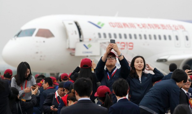 Attendees take photos in front of a Chinese C919 passenger jet after its first flight at Pudong International Airport in ...