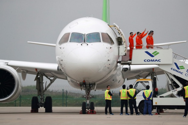 Flight crew members wave as they exit a Chinese C919 passenger jet after its first flight at Pudong International ...