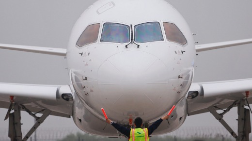 A member of staff gives signal in front of China's home-grown C919 passenger jet after it landed on its maiden flight at ...