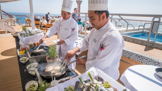 Viking Star chefs cooking fresh Norwegian fish on the terrace of the World Cafe.