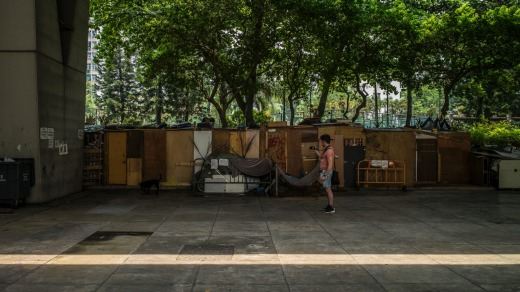 A tourist takes photos of makeshift homeless shelters, while on a tour with Alla Lau from Hong Kong Free Tours.