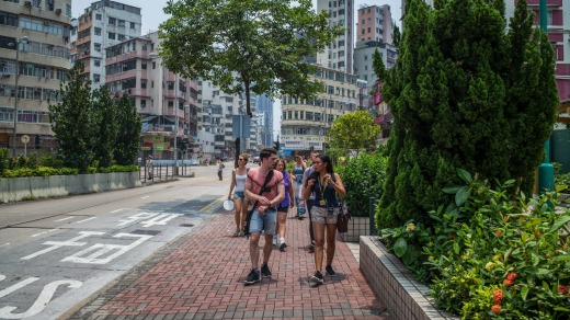Alla Lau, right, a travel guide, right, from Hong Kong Free Tours, leads tourists through the Sham Shui Po section of ...