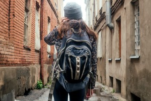 Girl tourist walking down the street on the back of a backpack. Photo: Shutterstock