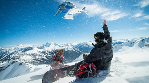 Snowboarders watch a helicopter take off after being dropped on a remote peak in Revelstoke.