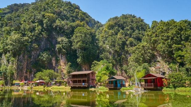 Wooden houses on Ipoh Lake, Malaysia. The limestone outcrops just outside town are reminiscent of Halong Bay in Vietnam.