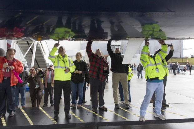 Attendees sign the fuselage of the Delta 747-400 at Paine Field in Everett.