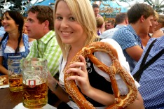C8WJN1 Young woman enjoying pretzel and stein of beer at Oktoberfest
