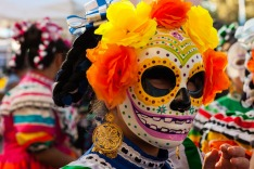 Girl wearing colorful skull mask and paper flowers for Dia de Los Muertos/Day of the Dead celebration