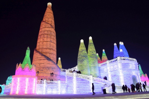 Visitors walk among the attractions at the Harbin International Ice and Snow Festival in Harbin in northeastern China's ...