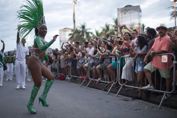 Members of a samba school parade along Copacabana Beach in Rio de Janeiro, Brazil. Musicians and members from Rio de ...