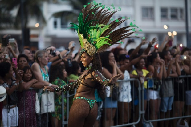 A member of a samba school parades along Copacabana Beach in Rio de Janeiro, Brazil. Musicians and members from Rio de ...
