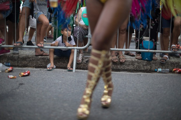 A child watches members of a samba school parading along Copacabana Beach in Rio de Janeiro, Brazil. Musicians and ...