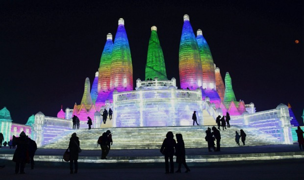 Visitors walk among the attractions at the Harbin International Ice and Snow Sculpture Festival in Harbin in ...