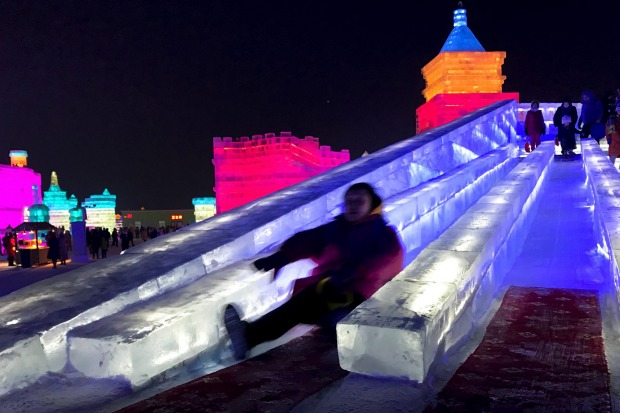 Visitors playing slide on a castle-like structure made from blocks of ice at the annual Harbin International Ice and ...