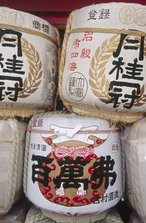 Three traditional sake barrels stacked up outside the temple wall.