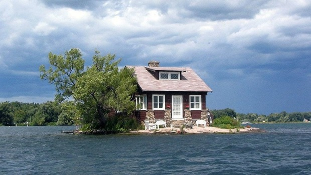 Just Enough Room Island just about manages to hold a cottage, a tree, shrubs and a tiny beach patch.