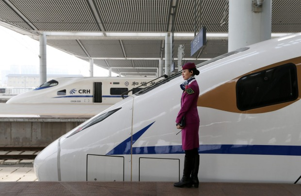An attendant stands beside a CRH (China Railway High-speed) bullet train on the Xi'an Chengdu high-speed railway.