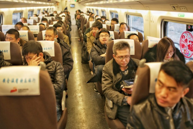 Passengers sit in a bullet train on the Shijiazhuang-Jinan high-speed railway at the Shijiazhuang Railway Station in ...