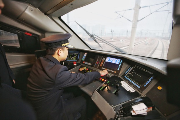 A driver in a bullet train about to leave the Shijiazhuang Railway Station.