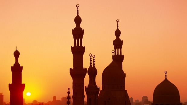 Domes and minarets dot the skyline at sunset in Cairo.