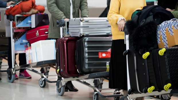 Travellers wait in line to check-in with luggage.