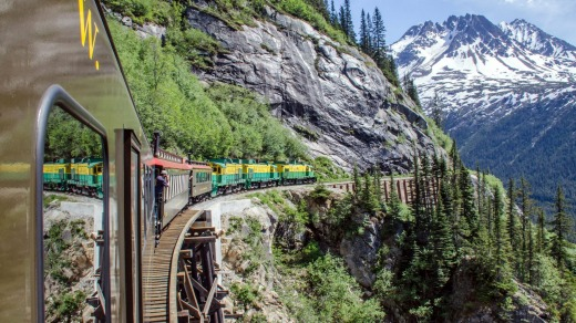 White Pass and Yukon Route Railroad travels along the cliffs heading towards Skagway, Alaska.