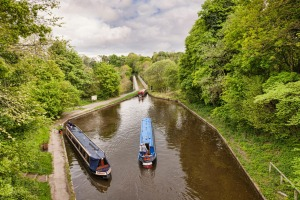 Narrowboats in the Llangollen Canal, built by Thomas Telford, manoeuvering before crossing the Chirk Aqueduct.