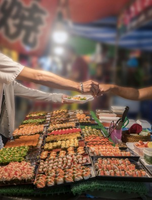 Buying sushi at a local market stall.