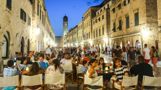 People on the terrace of the restaurant on the main city street Stradun at sunset in Dubrovnik, Croatia.