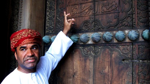 An Omani tour guide explains the meaning of words on the gate of Al Hazm Fort.