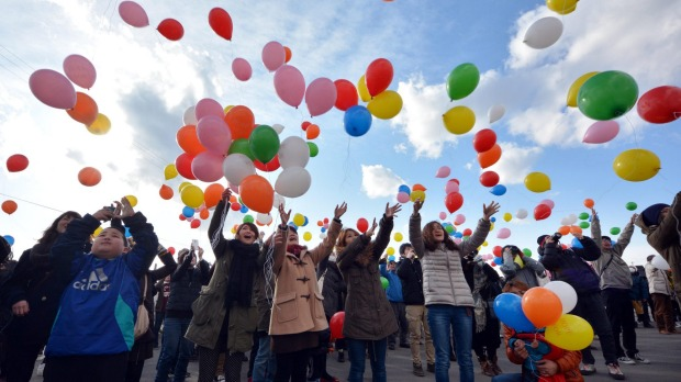 Bereaved families, relatives and friends release balloons as they visit Arahama Beach.