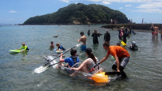 Launching in a Clearyak from the beach. It's important to avoid scratching the undersides of the kayaks so a staff ...