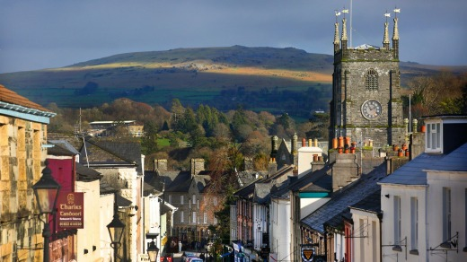 West Street in Tavistock, Devon, showing Tavistock Parish Church, with Dartmoor National Park in the background.